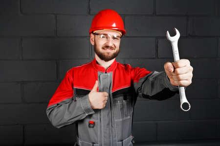 casco rojo: guardapolvos hombre vistiendo con casco rojo y una llave cerca de la pared de ladrillo Foto de archivo