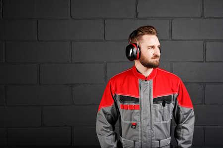 overol: guardapolvos hombre vistiendo con auricular profesional en la pared de ladrillo