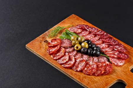 smoked sausage: assortment smoked sausage slices on cutting board Stock Photo