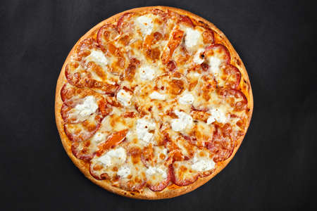 Hot tasty delicious rustic homemade american pizza with salami hamon mozzarella witj thick crust on black table