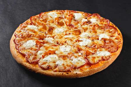 Hot tasty delicious rustic homemade american pizza with salami hamon mozzarella witj thick crust on black table