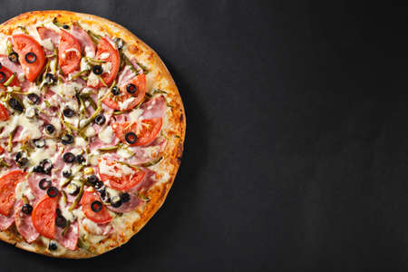 hot tasty delicious rustic homemade american pizza with tomato gherkin salami olives   with thick crust on black table