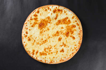 pizza crust: Hot four cheeses delicious rustic homemade american pizza with thick crust on black table Stock Photo