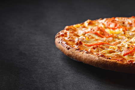 hot tasty delicious rustic homemade american pizza with pineapple chicken tomato with thick crust on black table Фото со стока