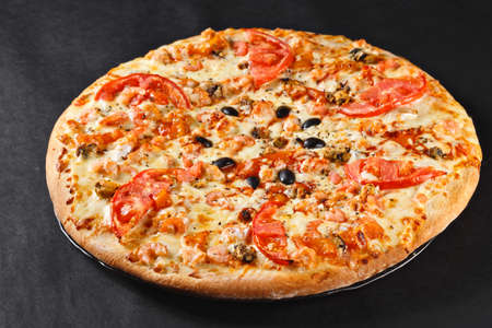 hot tasty delicious seafood homemade american pizza with shrimps with thick crust on black table
