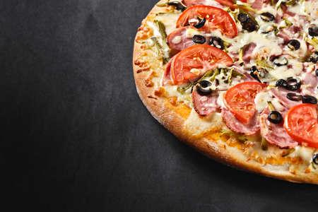 pizza: sabrosa deliciosa pizza casera rústico caliente americana con tomate aceitunas salami pepinillo con corteza gruesa en la mesa de negro