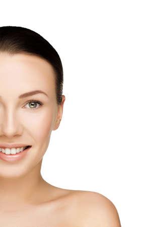 nudo integrale: mezzo volto di giovane e bella donna bruna con la pelle fresca e pulita con il trucco nude guardando dritto e sorriso. Primo piano foto reale