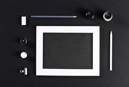 pintor: blanco maqueta con el blanco Marco de madera con el campo negro y negro y un conjunto de gouache acuarelas. Artista Pintor de trabajo Foto de archivo