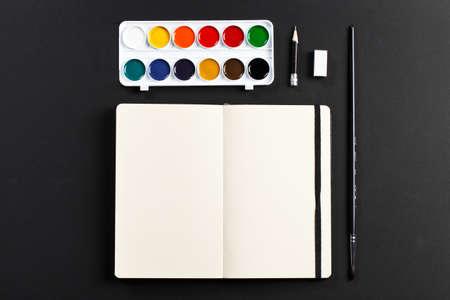 open book: Libreta en blanco abierto con p�ginas en blanco vac�os que ponen con la paleta de colores del agua l�piz cepillo de goma en el fondo negro. ideal para texto Foto de archivo