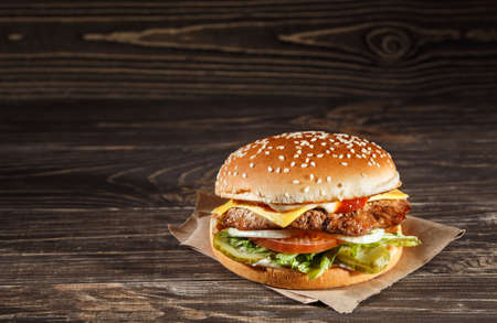 papas fritas: Queso hamburguesa con carne a la parrilla, queso, tomate, sobre el papel del arte en la superficie de madera. Plantilla de la comida rápida.