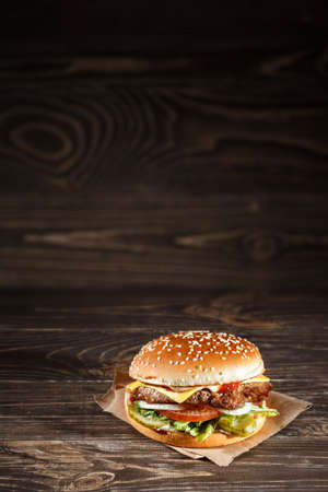 Cheese burger with grilled meat, cheese, tomato, on craft paper on wooden surface. Fast food template. Reklamní fotografie