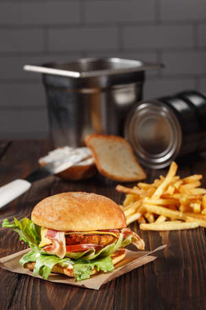 combo: tasty chicken burger with french fries on wooden table in kitchen. fast food template. unhealthy food