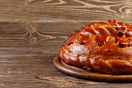 russian cuisine: Russian wedding round loaf close-up on wooden table. Wedding bread with salt. Russian wedding ceremony