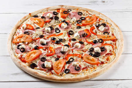 olive: Delicious fresh pizza with olive tomato and mozzarella served on wooden table. traditional italian pizza
