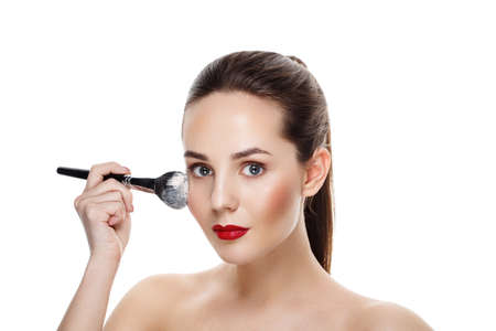 Beauty Girl with brush finish makeup apply highlighter. Bright Makeup for Brunette Woman with Beautiful Face. Makeover. Perfect Skin. Applying Make-up. Ideal for commercial