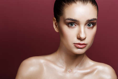 Beauty Portrait of Pretty Woman with Strobing Makeup. Wet Body Effect. Strobing or Highlighting makeup technique. Professional Retouch and Studio Photo. Ideal commercial concept. Vinous background