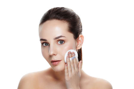 beauty and spa, cosmetology and relaxation concept - beautiful young woman having face cleaning by sponge. Fresh woman with sponge cleaning her face. isolated with clipping path