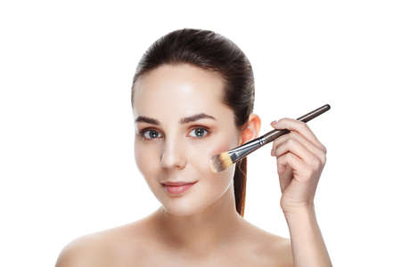 Beauty woman with Makeup Brushes. Natural Makeup for Brunette Woman with blue Eyes. Beautiful Face. Makeover. Perfect Skin. Applying Make-up. Ideal for commercial Reklamní fotografie