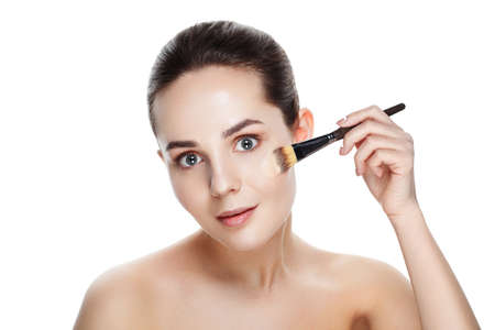 Beauty woman with Makeup Brushes. Natural Makeup for Brunette Woman with blue Eyes. Beautiful Face. Makeover. Perfect Skin. Applying Make-up. Ideal for commercial Фото со стока