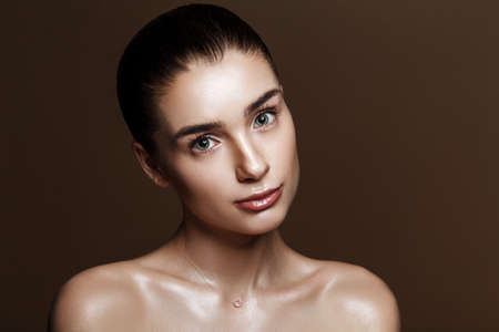 Strobing or Highlighting makeup. Closeup portrait of beautiful girl with strobing highlighter powder. Nice Glow. Perfect retouch. Studio photo beige background. Wet body effect