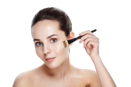 Beauty Girl with Makeup Brushes. Natural Makeup for Brunette Woman with blue Eyes. Beautiful Face. Makeover. Perfect Skin. Applying Make-up. Ideal for commercial Фото со стока