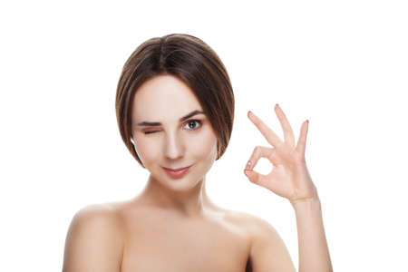 okey: Pretty girl with natural makeup show gesture OKEY. Beautiful spa woman touching her face. Perfect fresh skin. Pure beauty model girl. Youth and skin care concept