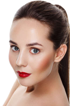 Beautiful young brunette model with red lips and blue eyes. Everyday makeup. Closeup Portrait. Isolated on white. Space for text. Ideal commercial photo for cosmetic company Фото со стока