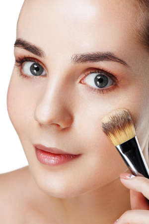 Closeup view of face of Beauty Girl with Makeup Brushes. Natural Makeup for Brunette Woman with blue Eyes. Makeover. Perfect Skin. Ideal for commercial. Part of face