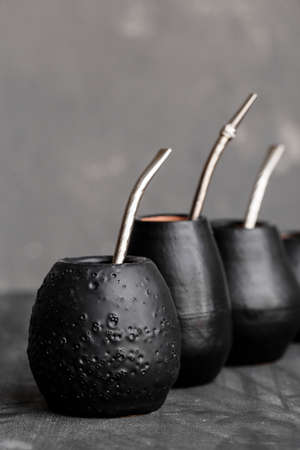 Black gourd with sipped metal straw best use for Yerba Mate tea. Famous hot drink in South America. Organic and natural.