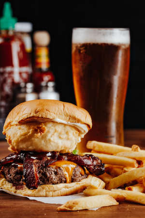 Mouth-watering bacon and angus beef burger flavored with crunchy fried onion, adding freshly cut potato fries on the side recommended for meat lovers.