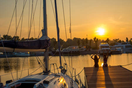 yacht club: Beautiful sunset at the yacht club. Sailing yacht at the berth. Yacht on the background of evening sun. Girls relax on the docks. Stock Photo