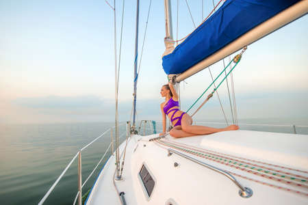 boat party: Beautiful girl sunbathing on the yacht. Rest on the yacht. Sailing yacht at the sea.