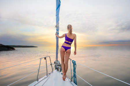 Evening walk on the yacht. Girl stands on the nose of the yacht and looking at the sunset. Romantic walk on the yacht. Beautiful view from the yacht. Zdjęcie Seryjne