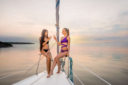 yacht club: Girlfriends relaxing on the yacht. Two girls celebrating a birthday on the yacht. Evening walk on the yacht on the sea. Stock Photo