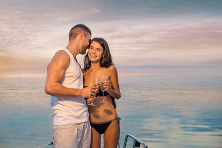 yacht: Guy with the girl relaxing on the yacht. Romantic trip. Couple drinking champagne. Loving couple relaxing on the yacht for the weekend.