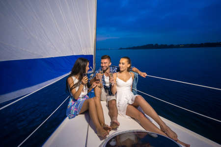 summer night: Youth party on a yacht. Friends drinking champagne. Night walk on a yacht. Stock Photo
