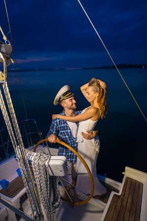 yacht club: Romantic trip on a yacht. Night walk along the river. Loving couple on a yacht. Honeymoon on the yacht.