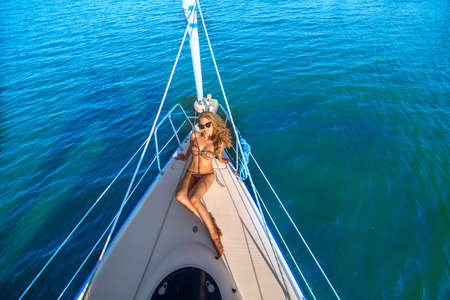 yacht club: Girl sunbathing on the bow of the yacht. Travel by sea on a yacht. Model on the boat. Summer holidays at sea.