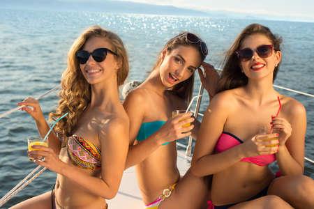 bateau: Girlfriends détente sur un yacht. Les filles à la mer. Croisière sur un yacht. Les filles sourient. Glamour fille de détente sur un yacht.