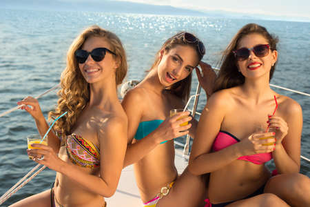 chicas sonriendo: Novias que se relajan en un yate. Muchachas en el mar. Cruise en un yate. Las niñas sonríen. La glamurosa relajándose en un yate. Foto de archivo