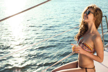 sailboat: Girl sunbathes on board the yacht. Yachting. Holiday on the ocean. Girl drinking juice on vacation.