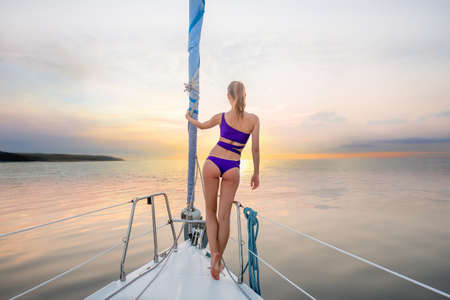 Evening walk on the yacht. Girl stands on the nose of the yacht and looking at the sunset. Romantic walk on the yacht. Beautiful view from the yacht. Stock Photo