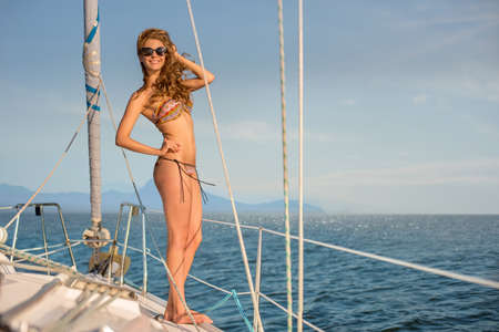 yacht club: Girl resting on the yacht. Walking by the sea on a yacht. Girl posing on a yacht. Sailing yacht. Summer vacation. Stock Photo