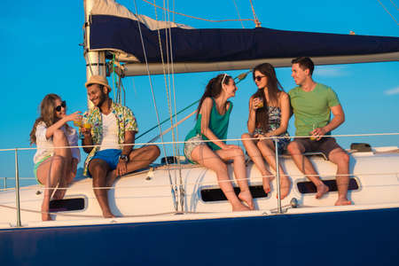 yacht club: Young people is resting on the sailing yacht. Corporate party on a yacht. Friends spend a weekend on a yacht. Event on the yacht. Merry company is celebrating a birthday on a yacht.