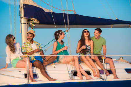 Cheerful young people relaxing on a yacht. Corporate party on a yacht. Friends spend a weekend on a yacht. Event on the yacht. Bandmates celebrating a birthday on a yacht.