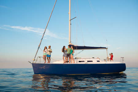 yacht club: Young people is resting on a sailing yacht at sea. Weekend on a yacht. Yachting. Cruise on a yacht on the ocean. Guys and girls are traveling on a yacht. Youth party on a yacht.