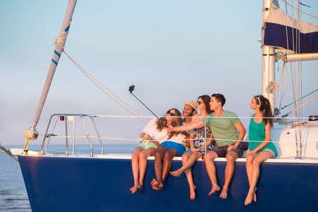 Jeugd maakt selfie op een jacht. Jongeren zijn gefotografeerd op een jacht. Vriendelijke bedrijf berust op een jacht. Vakantie op een jacht. Vrienden rusten in de zee. Stockfoto