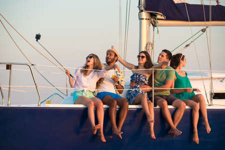 Merry company celebrates birthday on a yacht. Youth party on a yacht. Cruise on a sailing yacht. Friends making self on a yacht. Successful youth rests on a yacht. Stock Photo