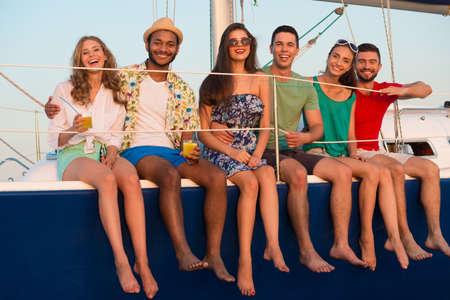 Liebevolle Paare Entspannung auf einer Yacht. Glückliche junge Leute Segeln auf der Yacht. Schöne Jungs und Mädchen verbringen das Wochenende auf einer Yacht. Kreuzfahrt auf einer Yacht auf dem Meer. Party auf einer Yacht. Standard-Bild
