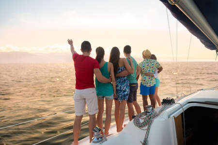Holiday on a sailing yacht. Loving couples relaxing on a yacht. Guys and girls on a sea voyage on a sailing yacht. Young people spend a weekend on a yacht at sunset. Cruise on a sailing yacht. Standard-Bild